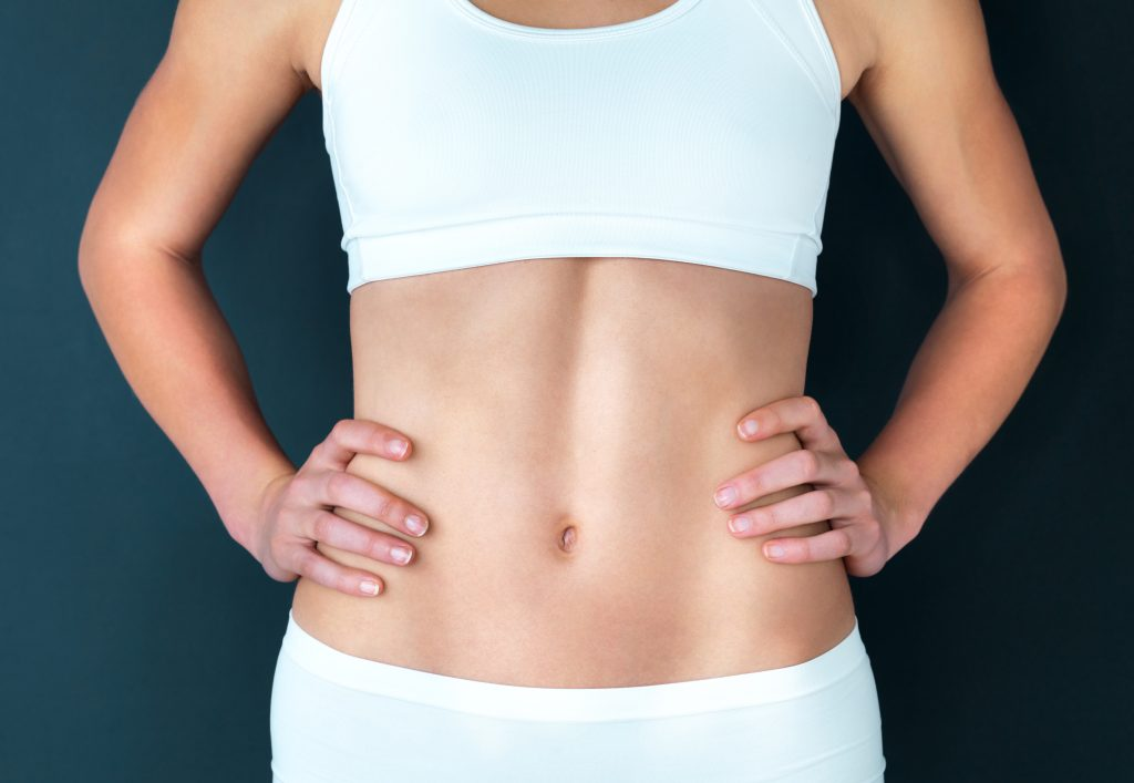 Woman's toned abdominals, wearing white under garments with hands on hips